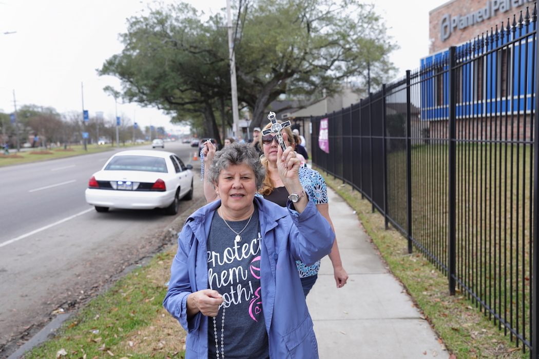 Karen Arnold, New Olreans native who frequently participates in anti-abortion events, prays with other protesters February 12, 2017, near the entrance to the South Claiborne Avenue Planned Parenthood location, New Orleans, Louisiana as part of a national protest against the establishment.