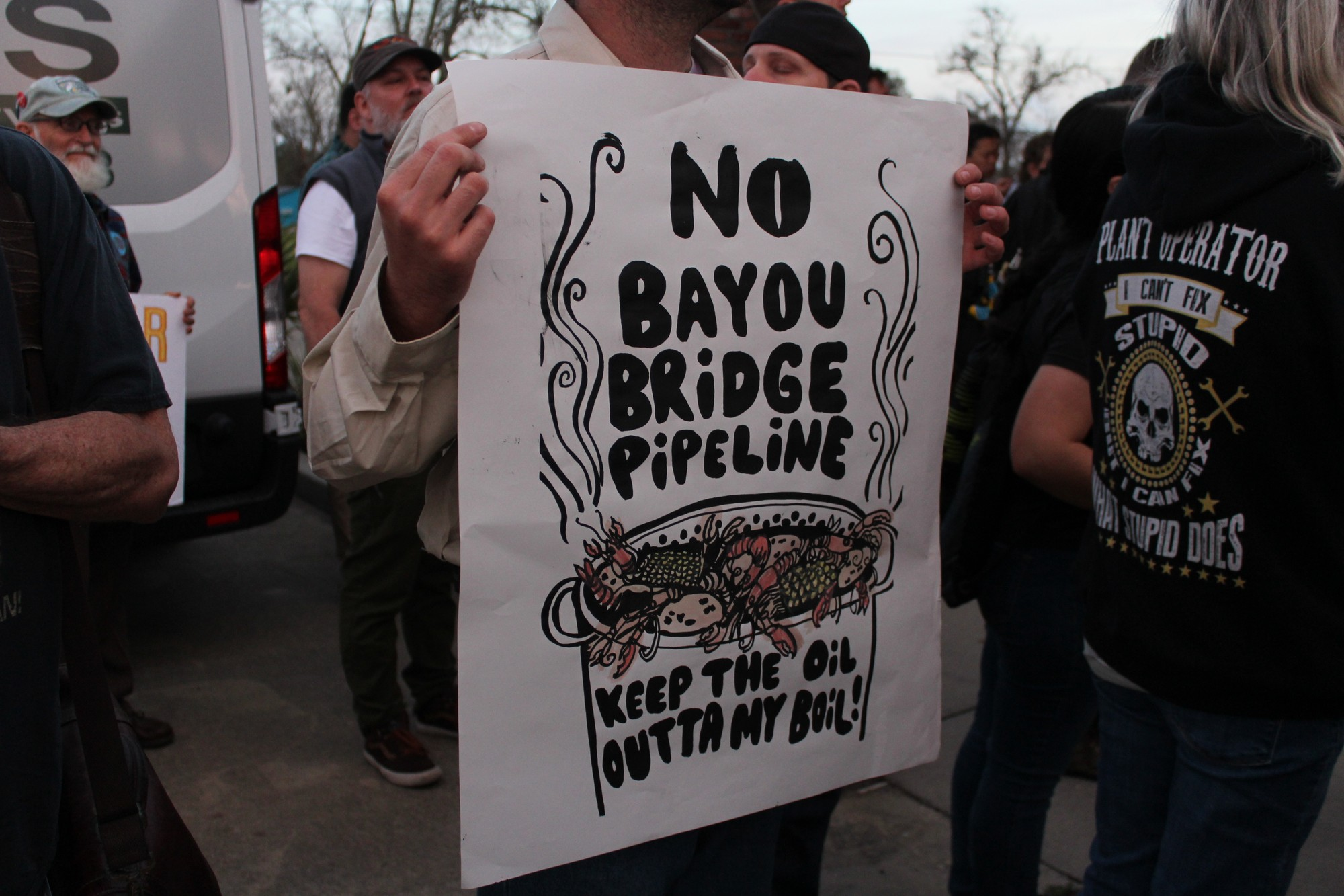 A protester holds up a sign prior to a hearing for the Bayou Bridge pipeline. Speakers at the hearing were often interrupted by protests from the crowd.
