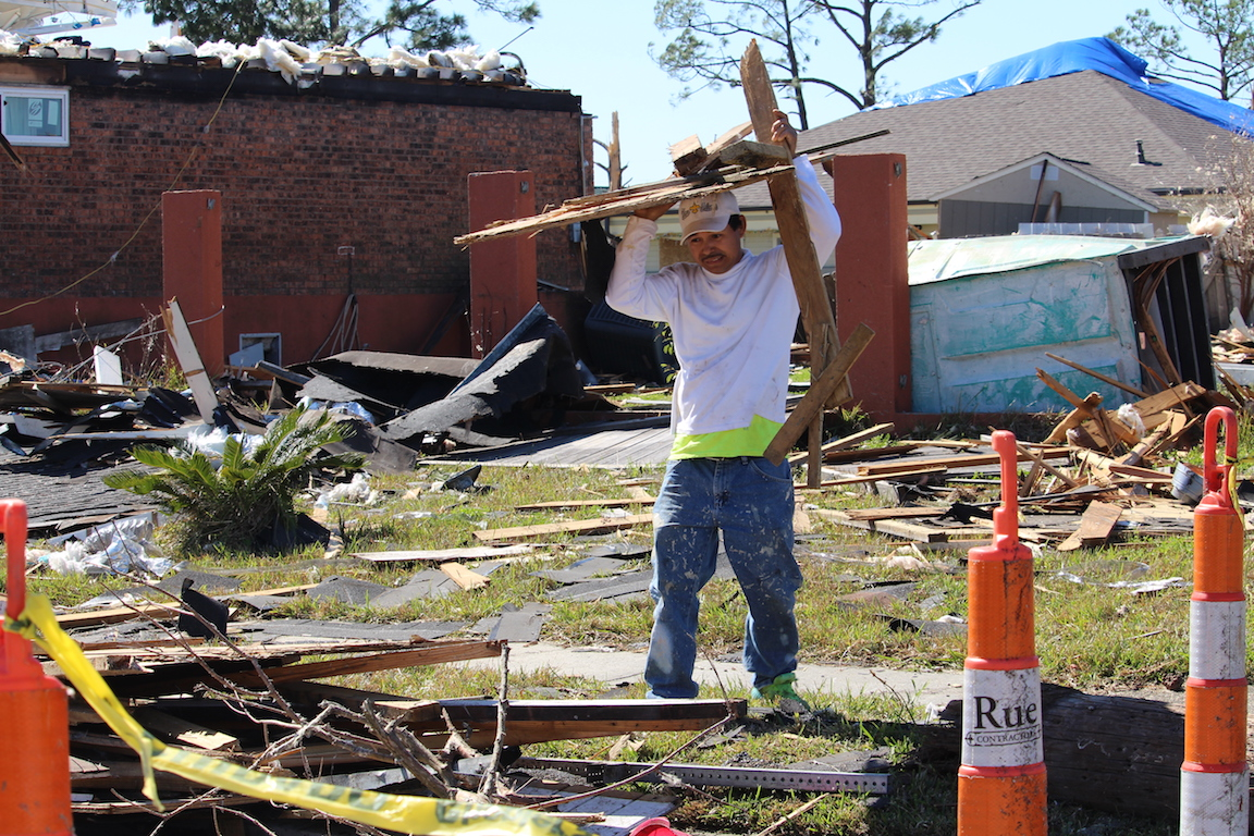A worker with Mr. Fix It helps to pile up the debris left after the storm. Shortly after the storm, volunteers from all over came to aid those affected by the storm.