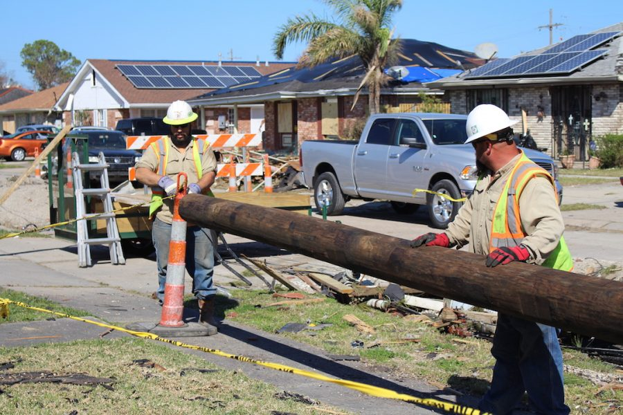 Two construction workers move an electricty pole from the street on Feb. 10. The city hopes to remove all the debris from the storm by the end of the month.
