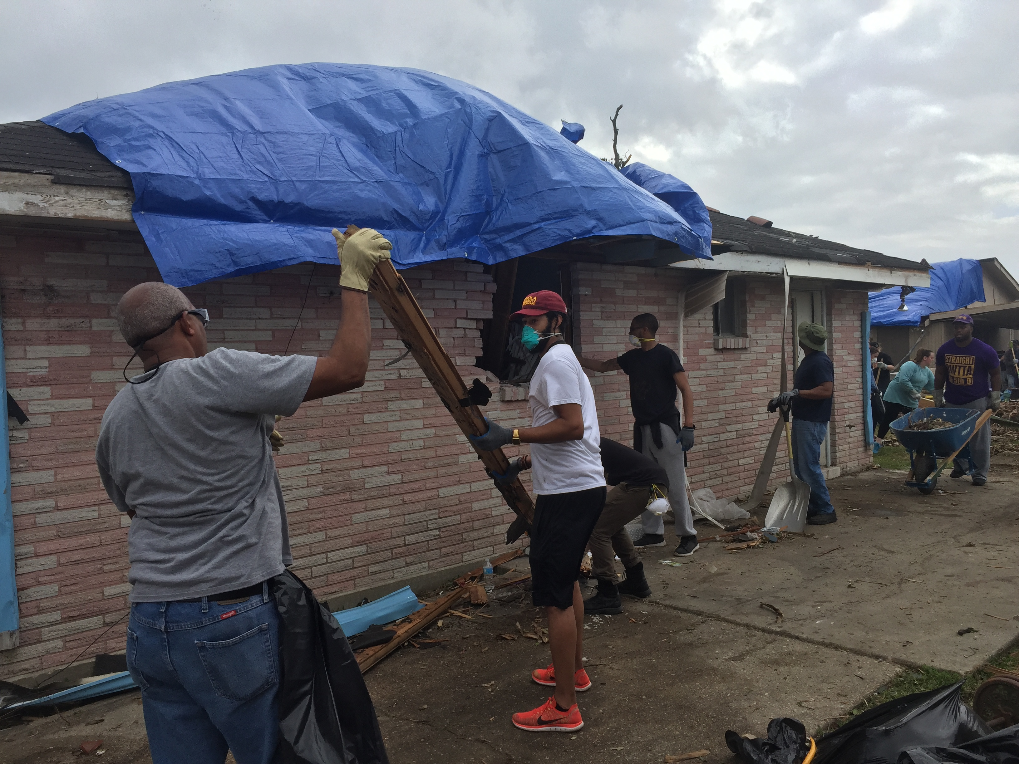 Loyola alumnus and Alpha Phi Alpha member, Eddie Murray A'15, helps remove debris from Mims' bedroom window. Alpha Phi Alpha organized a group of volunteers to help clear debris Photo credit: Natalie Hatton