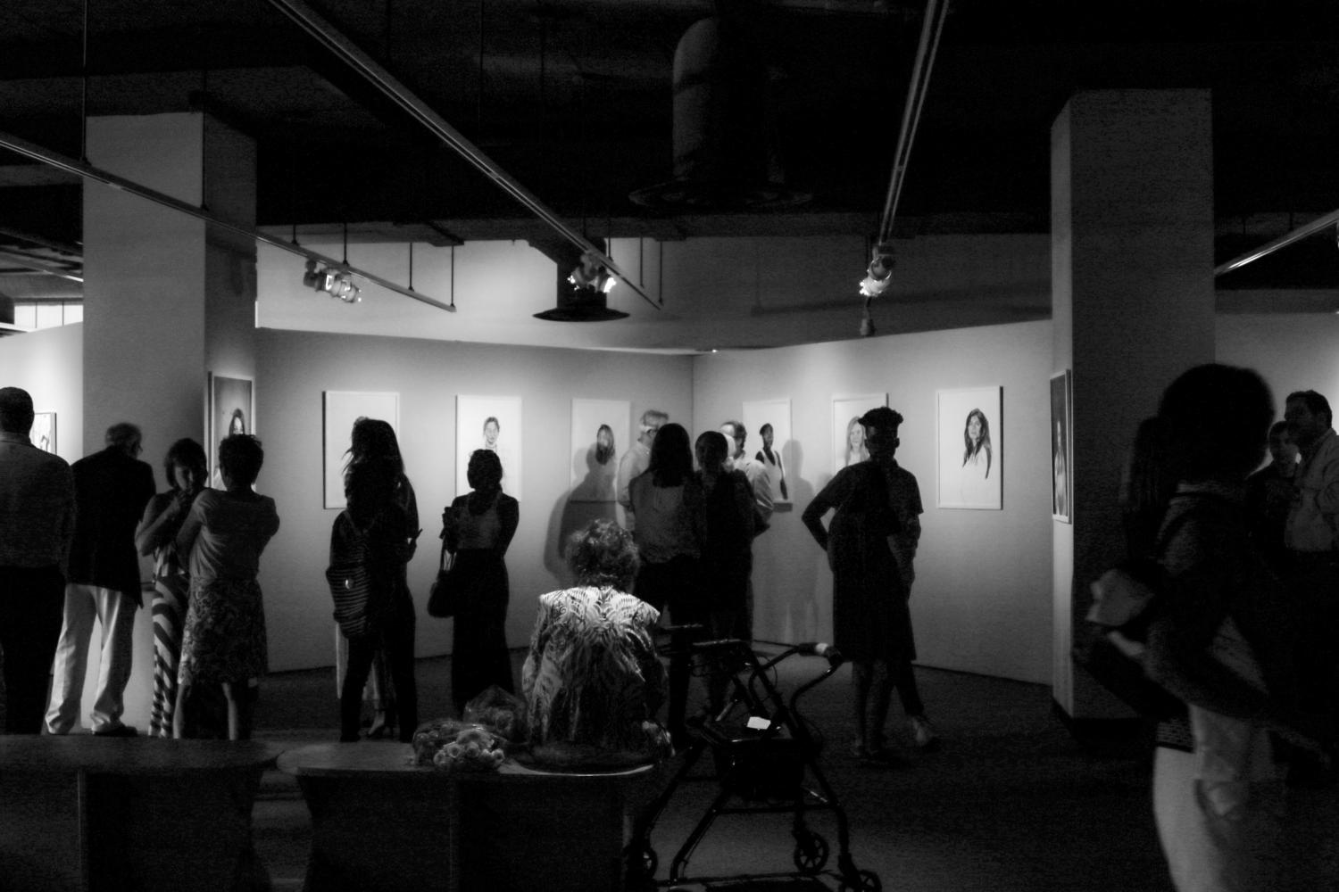 Attendees view the exhibits on display at The B.F.A. and B.A. Senior Show in the Colins C. Biboll Art Gallery. The six seniors present showcased their four years of visual art tutelage Photo credit: Matthew Dietrich