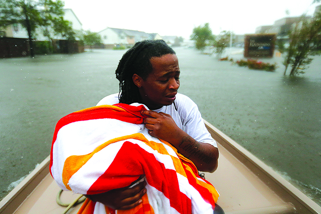 Demetres Fair holds a towel over his daughter Damouri Fair, 2, as they are rescued by boat by members of the Louisiana Department of Wildlife and Fisheries and the Houston Fire Department during flooding from Tropical Storm Harvey in Houston, Monday, Aug. 28, 2017. (AP Photo/Gerald Herbert) Photo credit: Associated Press