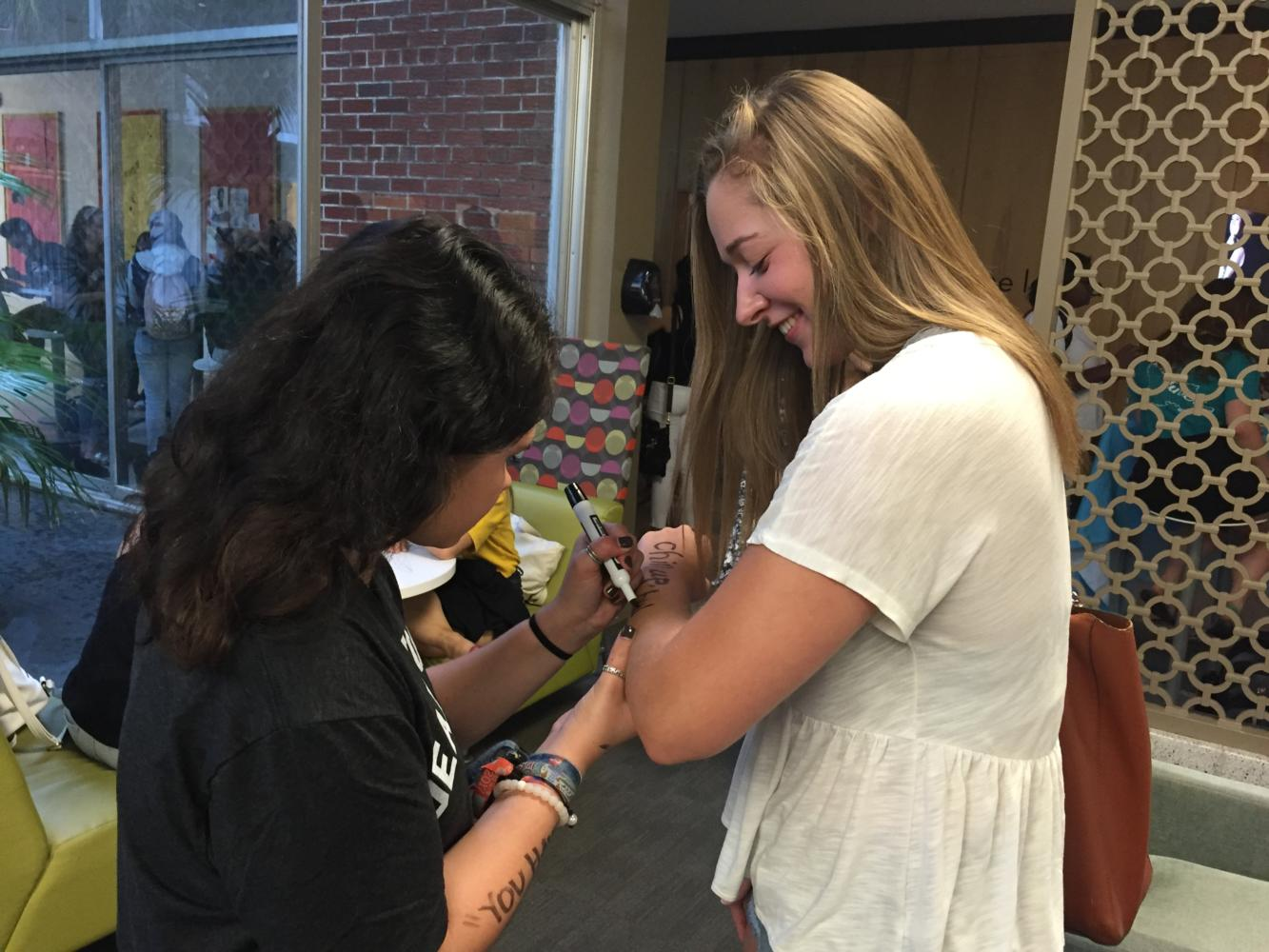 Brianna Daniel, history junior, writes a message on Brittany Webb, biology sophomore, for the Dear World event held in The Danna Center. Dear World is a photo storytelling project that has visited hundreds of college campuses. Photo credit: Erin Snodgrass