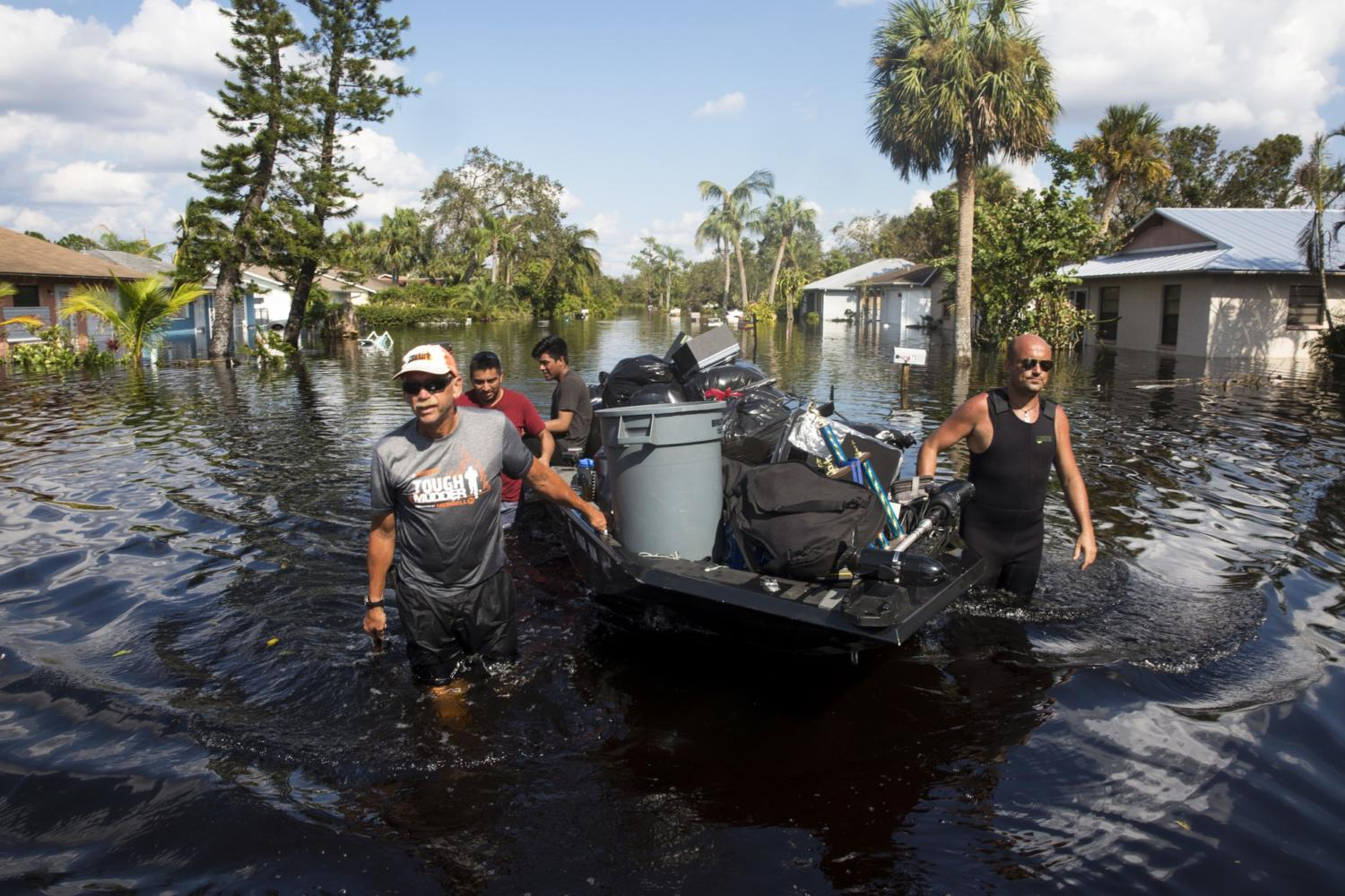 Don Manley, left, and Pedro Castellano, right, pull Manley's boat, loaded with residents' belongings, along a flooded Chapman Avenue in Bonita Springs, Fla., on Friday, Sept. 15, 2017, in the aftermath of Hurricane Irma.   (Nicole Raucheisen/Naples Daily News via AP) Photo credit: Associated Press