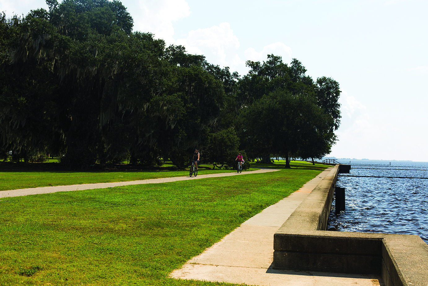 Cyclists+ride+down+Mandeville%27s+lakefront+on+a+sunny+day.+The+seawall+pictured+is+regularly+overtopped+during+tropical+systems%2C+leading+to+inland+flooding.+Photo+credit%3A+Barbara+Brown