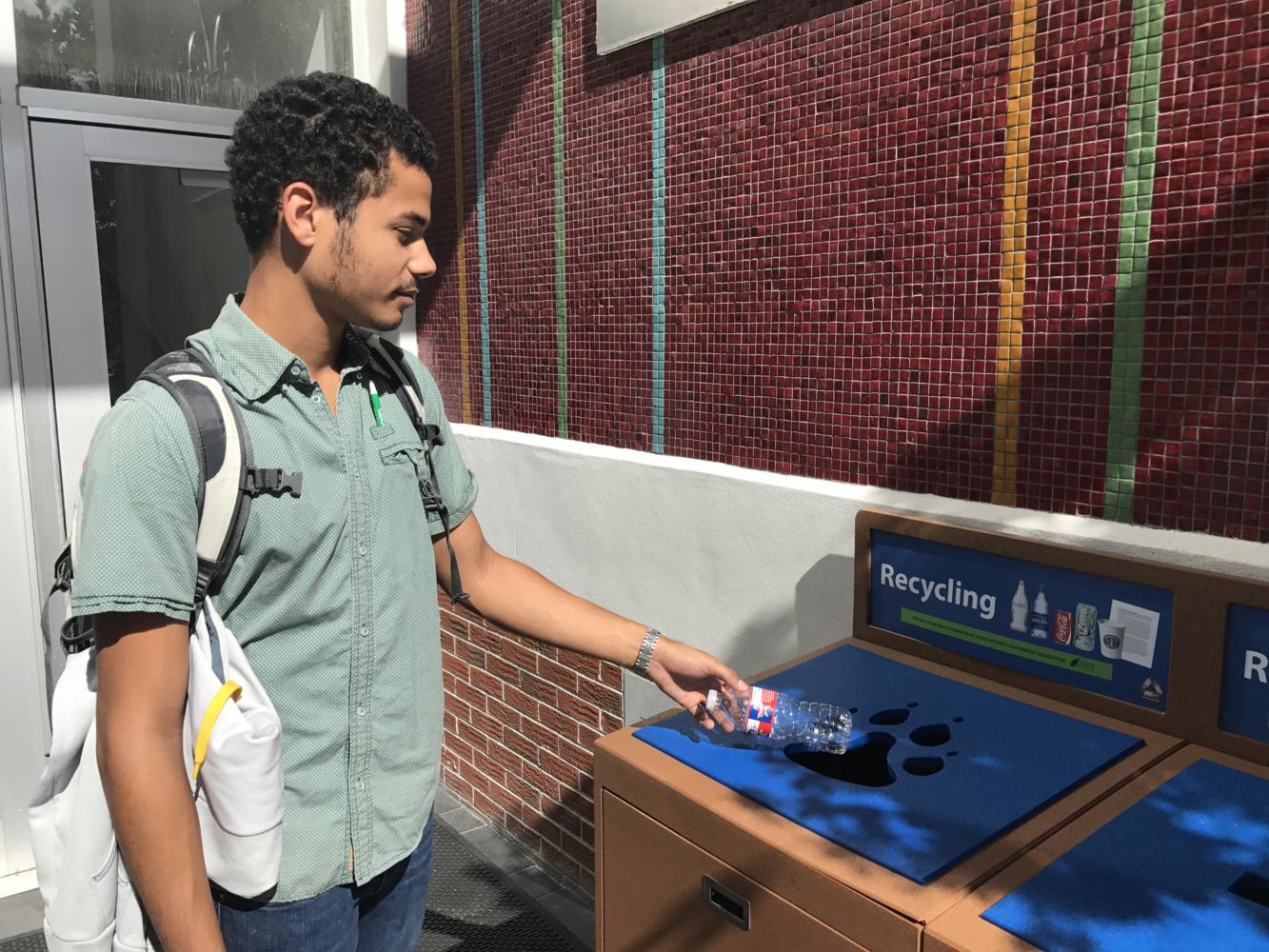 A student walks out of the Dana Center on Loyola University's campus and tosses a bottle into nearby recycling bins.  The new bins were intended to be more attractive and unique with hopes of enticing individuals to use them more frequently. Photo credit: John Casey