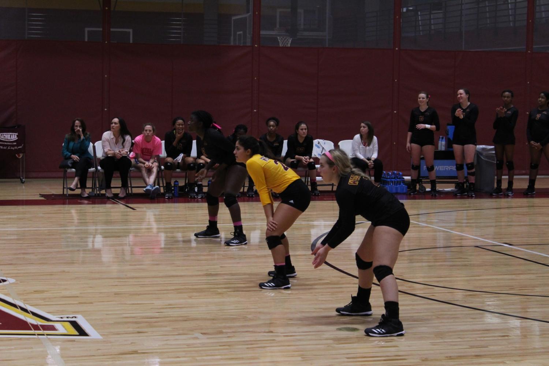 Volleyball players Natavia Mitchell, Kaitlynn Mitchell, and wait to counter a shot. Photo credit: Cristian Orellana
