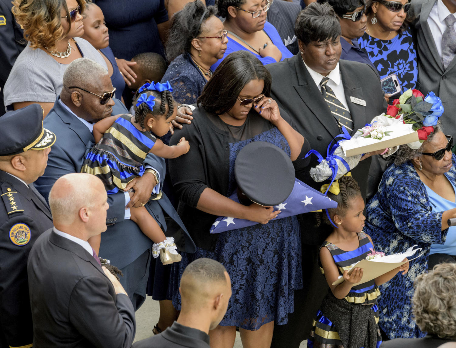 Brittiny McNeil holds the hat and flag of her late husband New Orleans Police Officer Marcus McNeil while she is comforted by her daughter Camille McNeil, 2, left, next to her other daughter, Maisie McNeil, 5, bottom right, and McNeil's mother Kimberly McNeil, top right, and his grandmother Alvena McNeil at Mount Olivet Cemetery during his funeral in New Orleans, La., Saturday, Oct. 21, 2017. New Orleans Police Department Superintendent Michael Harrison, left, and Mayor Mitch Landrieu, second left, stand with hands over their hearts. McNeil, 29, was shot and killed Oct. 13 during a routine patrol. (Matthew Hinton/The Advocate via AP) Photo credit: Associated Press