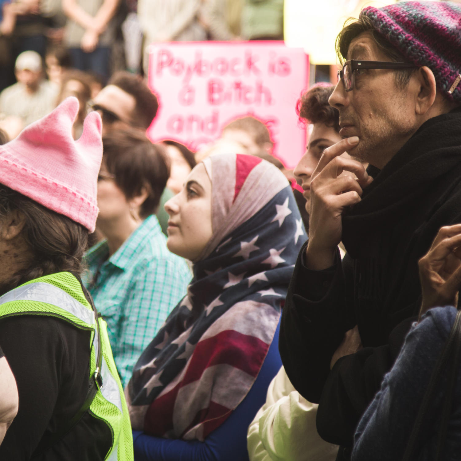 A Muslim woman wearing an American flag hijab as she listens to the keynote speeches. Trump's immigration travel ban was a major issue addressed by the Women's March Photo credit: Matthew Dietrich