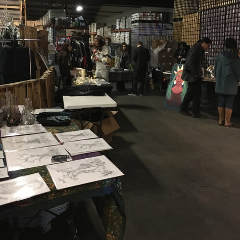 Market goers observe various artwork at Portculture Saturday, Jan. 20th, 2018, at the Urban South Brewery on Tchoupitoulas Street. Several students and young local artists sold their artwork at the event. Photo credit: Kaylie Saidin Photo credit: Kaylie Saidin
