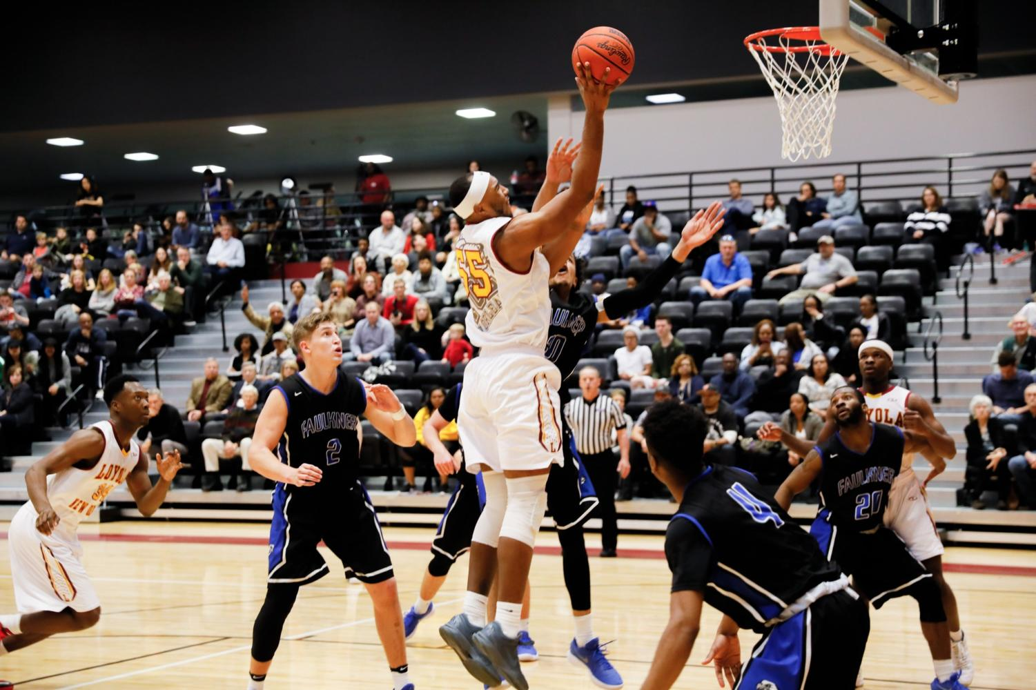 Senior, #55 Benjamin Fields, rebounds and shoots the ball. Fields led the team with a total of 14 points at the Faulkner University game in the den Jan. 20, 2018. Photo credit: Julia Santos