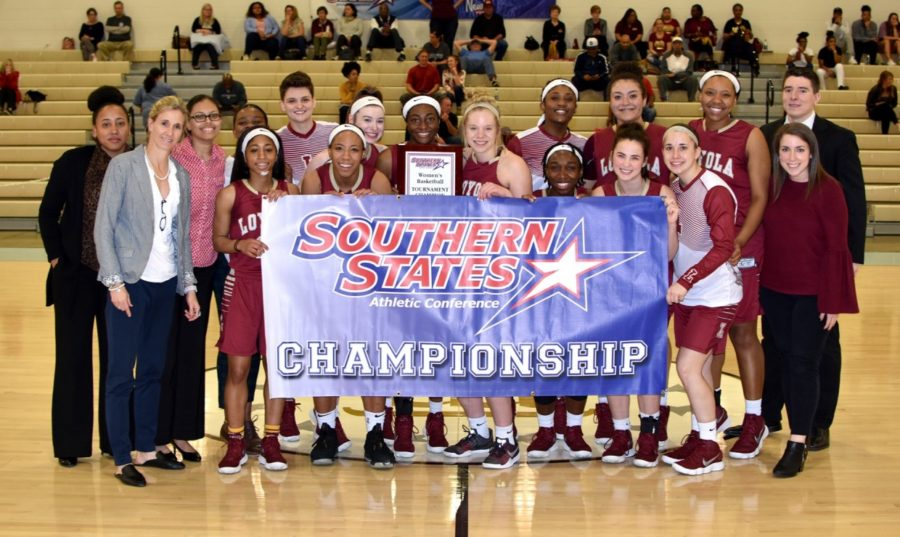 The+2017-2018+Loyola+women%27s+basketball+team+poses+with+the+championship+banner+after+their+66-53+win+versus+Martin+Methodist.+The+program+celebrates+their+third+championship+in+four+years.+Photo+credit%3A+Loyola+University+Athletics