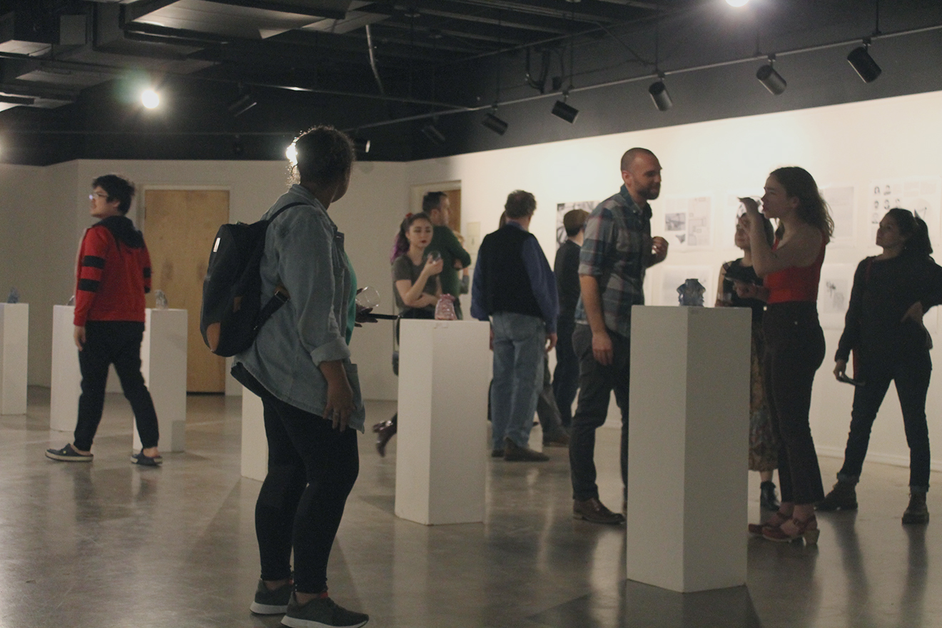 Patrons mill and examine art pieces at the Scully Scholarship & Grote Award Show on Thursday, Feb. 22nd, 2018. Every year, three students from the Art and Design Departments are selected to exhibit their work in the show. Photo credit: Jacob Schmitt
