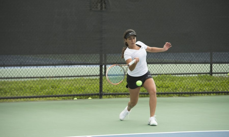 Koral Martinez, biology junior, hits a serve on a tennis court. This season, the men's tennis team has a 6-4 record and the women's team has a 5-6 record. Photo credit: Loyola University Athletics