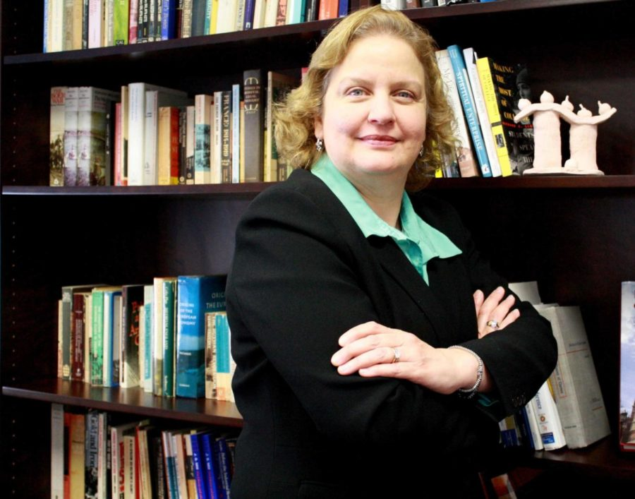 Maria Calzada, dean of the College of Arts & Sciences, poses in front of her bookshelf. Calzada will assume the position of interim provost.