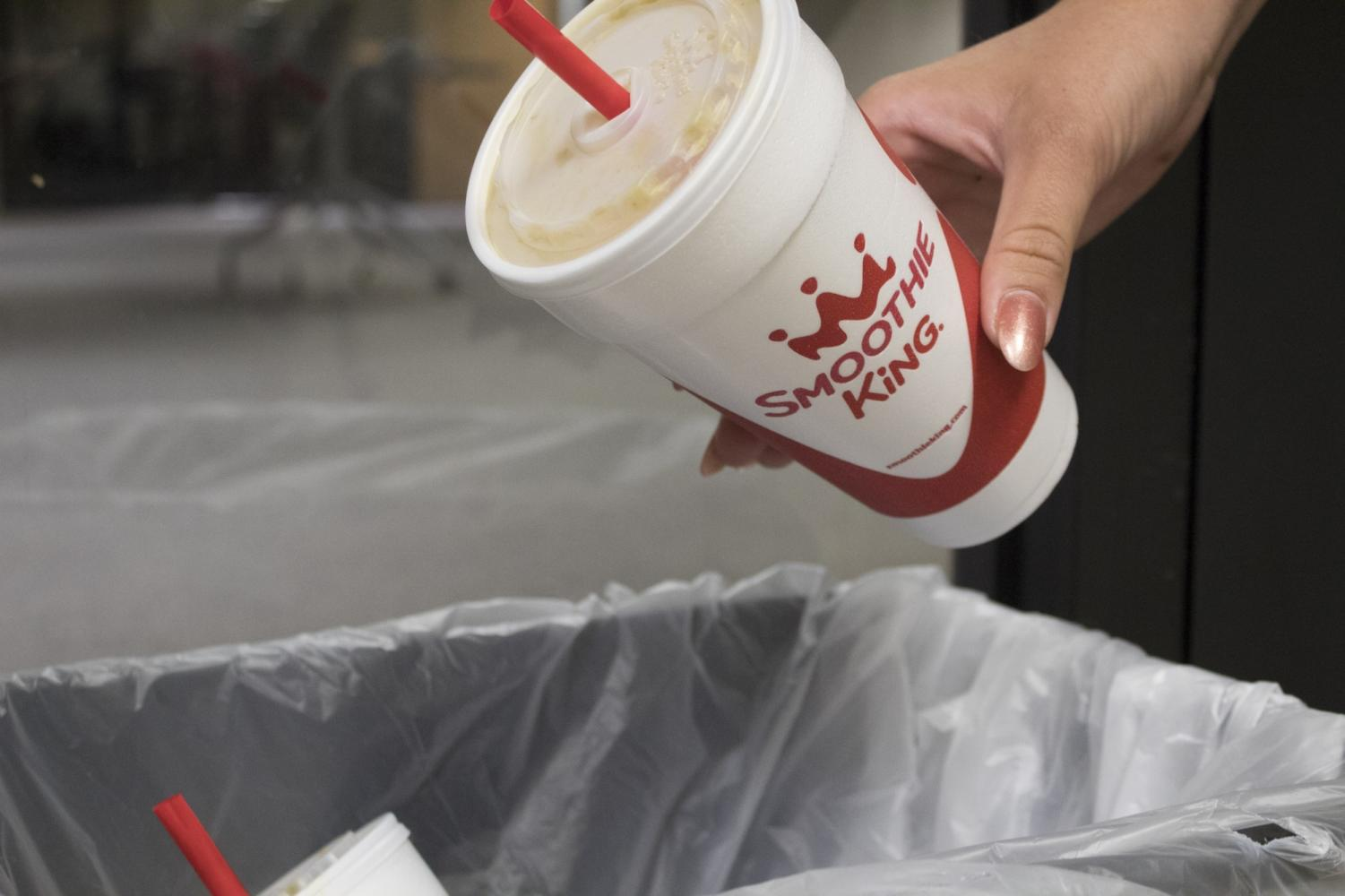 A student throws away a non-recyclable Smoothie King cup in the Communications and Music Complex. Garretty is frustrated with the lack of eco-friendly options at Loyola's Smoothie King. Cristian Orellana // The Maroon Photo credit: Cristian Orellana