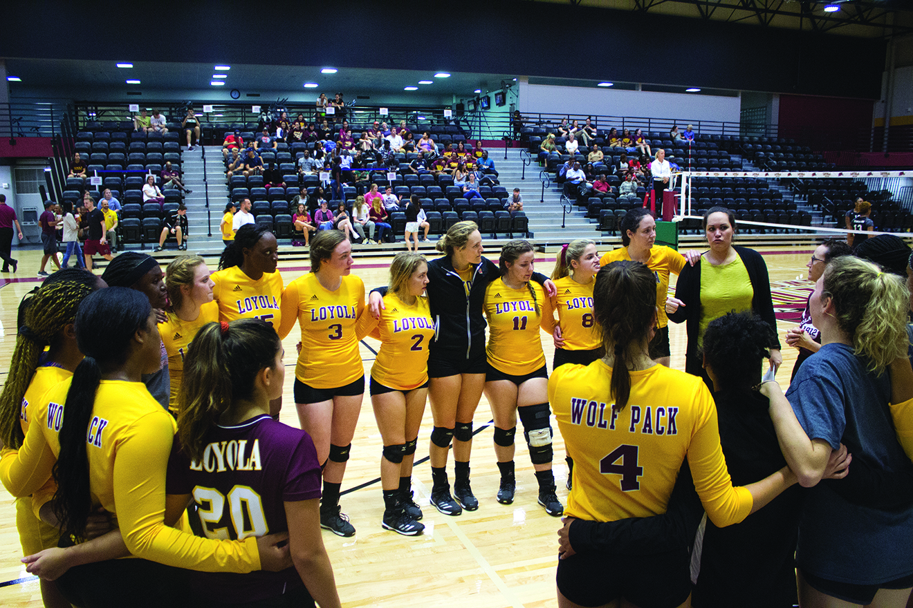 The Loyola volleyball team gathers in a group huddle during the game. The volleyball team has achieved record-breaking success under Jesse Zabal's first year as head coach. Photo credit: The Maroon