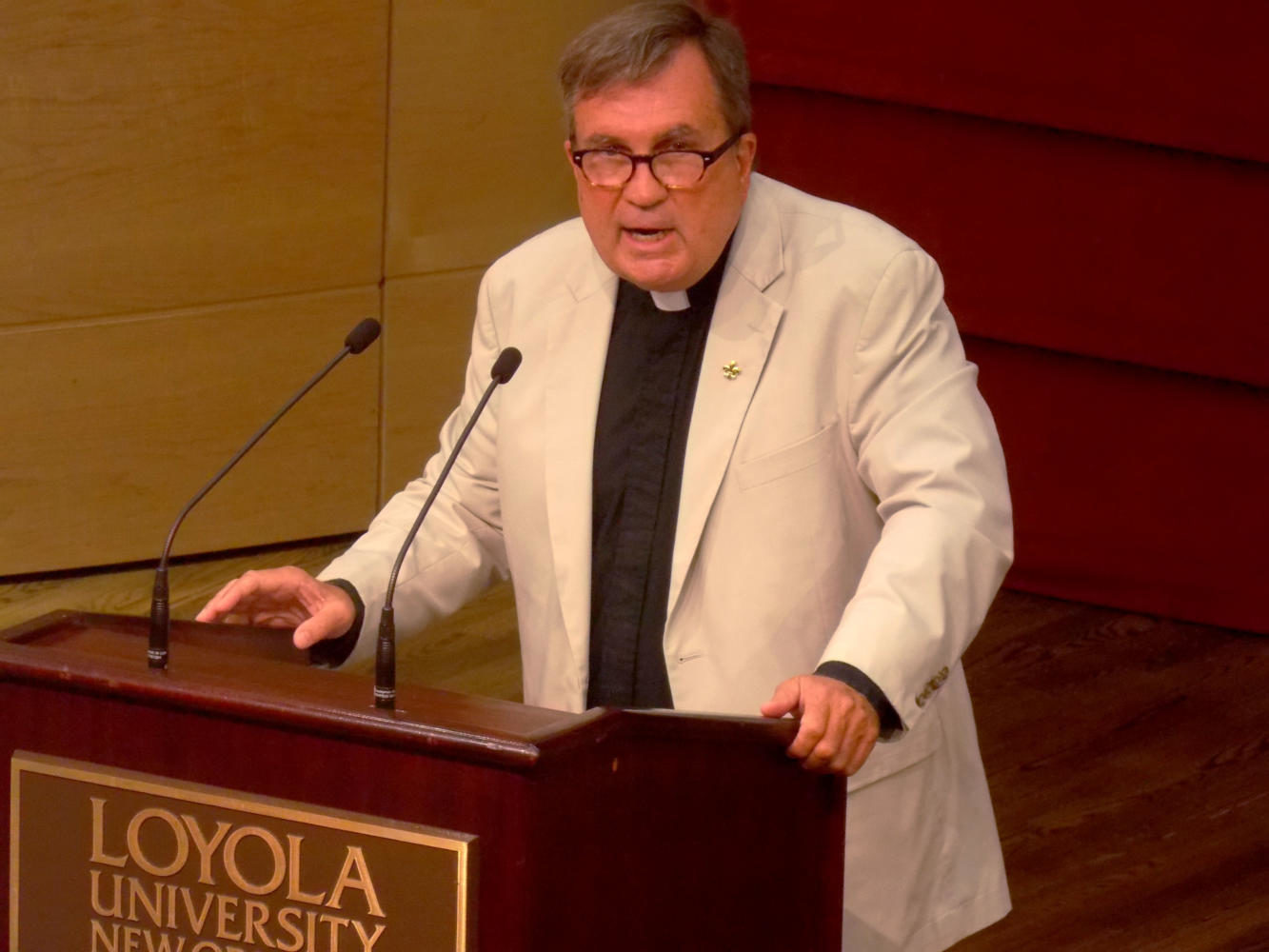 The Rev. Kevin Wildes, S.J., university president, addresses faculty at a convocation. Photo credit: The Maroon