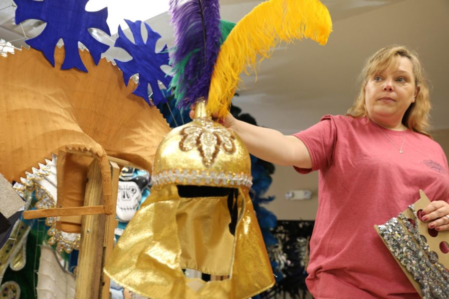 Missy Hildreth holds up a helmet used in a Mardi Gras parade. Hildreth and her team specialize in all things Mardi Gras apparel. Photo credit: Andres Fuentes