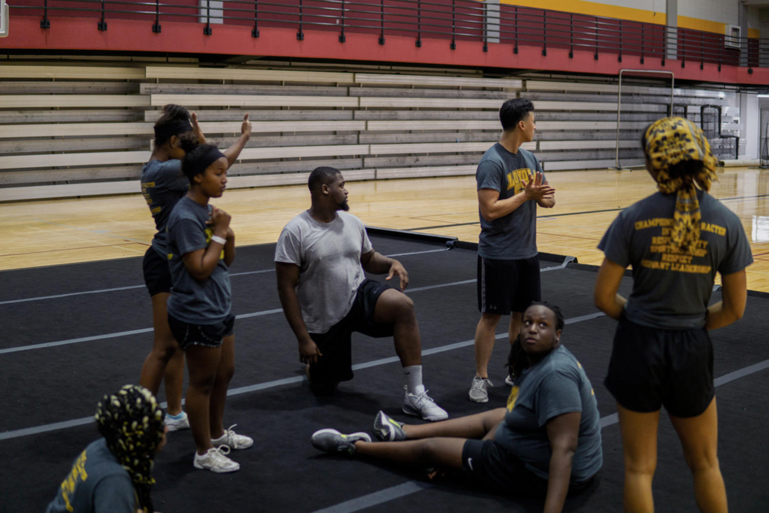 Tri Le, third from the right, looks on as he and members of Loyola's competitive dance team rest between iterations of formations they practice early on Tuesday morning. Photo credit: Jacob Meyer