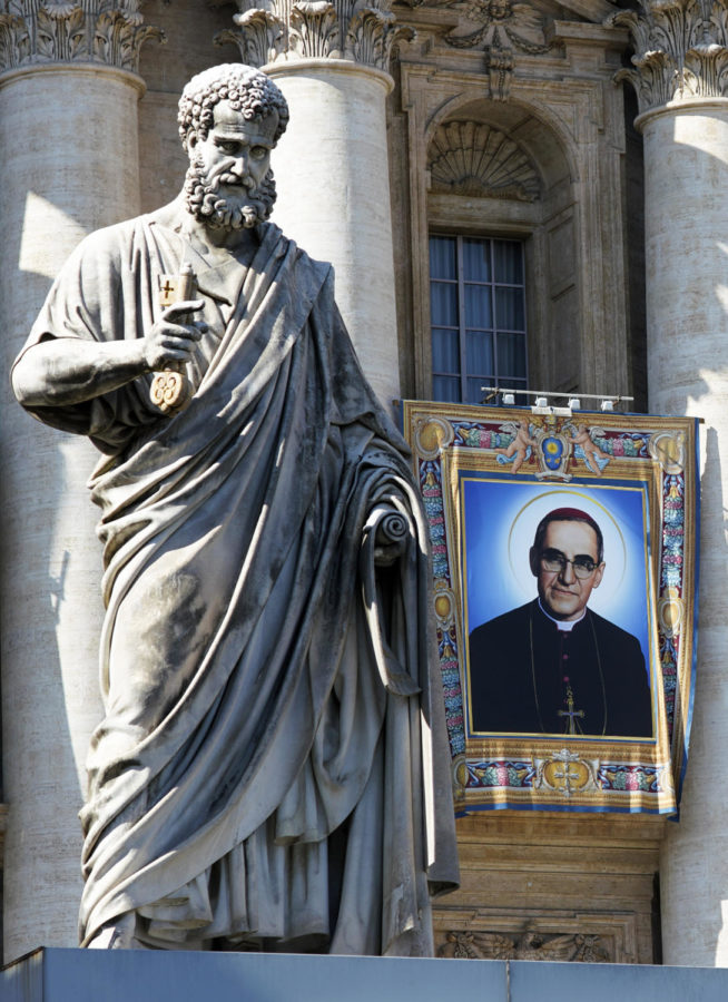 A man holds a poster of Archbishop Oscar Arnulfo Romero during a precession, in San Salvador, El Salvador, Saturday, Oct. 13, 2018.  SALVADOR MELENDEZ/AP.