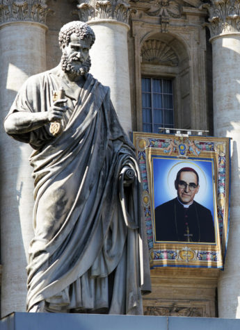 The tapestry of Roman Catholic Archbishop Oscar Romero hangs from a balcony of the facade of St. Peter's Basilica at the Vatican, Saturday, Oct. 13, 2018. Pope Francis will canonize two of the most important and contested figures of the 20th-century Catholic Church, declaring Pope Paul VI and the martyred Salvadoran Archbishop Oscar Romero as models of saintliness for the faithful today. (AP Photo/Andrew Medichini)
