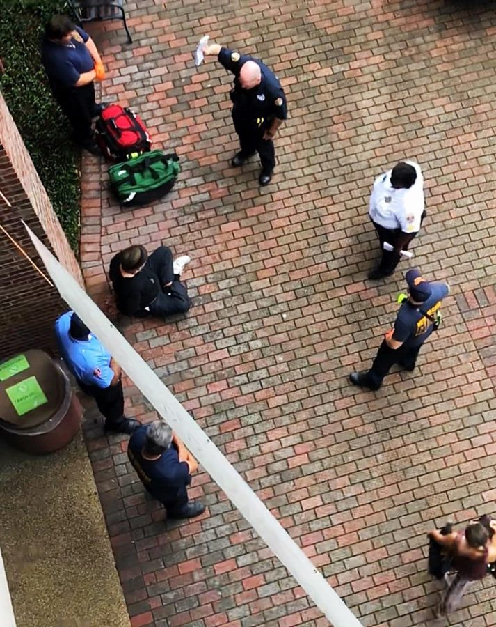 Robert Neville, sitting and hand cuffed on the ground, is surrounded by LUPD officers, EMS and a NOPD. Neville has been issued a summons to court for a criminal trespassing violation. Photo credit: Andres Fuentes