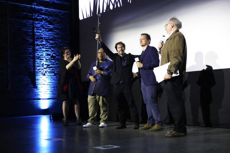 Tim Blake Nelson (middle), the actor who plays Don Quixote in The True Don Quixote,  hoists a sword used as a prop in the film given to him by the director Chris Poché. The True Don Quixote premiered at the 2018 New Orleans Film Festival. Photo credit: Cristian Orellana