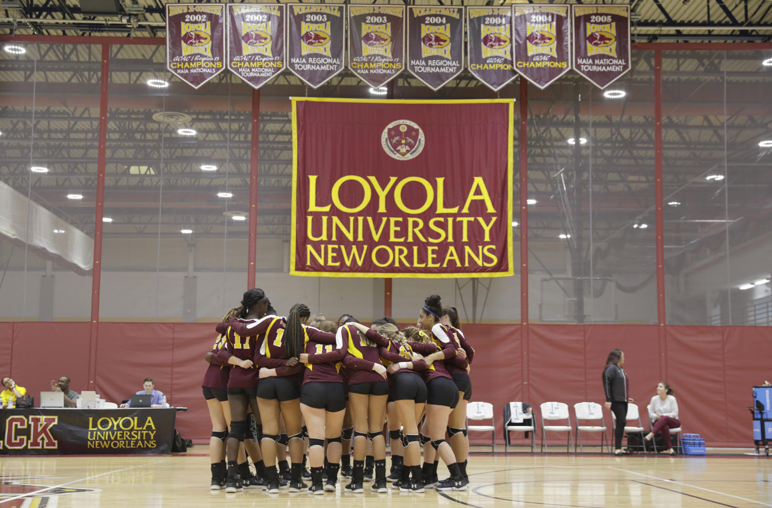 The Loyola's volleyball team huddles together at a home game. Photo credit: Cristian Orellana