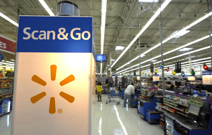 This Nov. 9, 2018, photo shows a Scan & Go checkout area at a Walmart Supercenter in Houston.  Retailers will once again offer big deals and early hours to lure shoppers into their stores for the start of the holiday season. But they'll also try to get shoppers out of their stores faster than ever by minimizing the thing they hate most: long lines. (AP Photo/David J. Phillip)