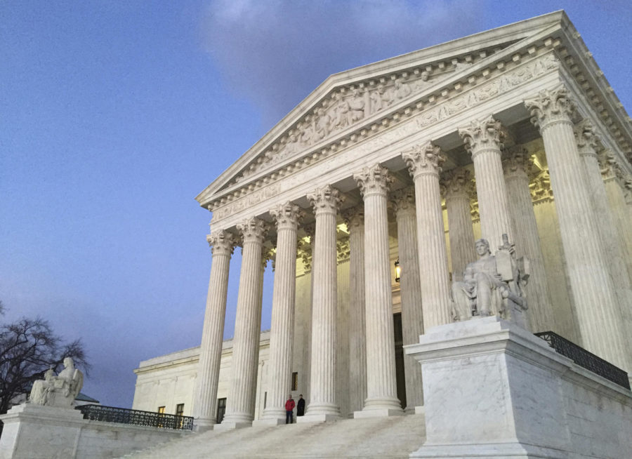 FILE - In this Feb. 13, 2016, file photo, people stand on the steps of the Supreme Court at sunset in Washington. A sharply divided Supreme Court is allowing the Trump administration to go ahead with its plan to restrict military service by transgender men and women while court challenges continue.  (AP Photo/Jon Elswick, File)
