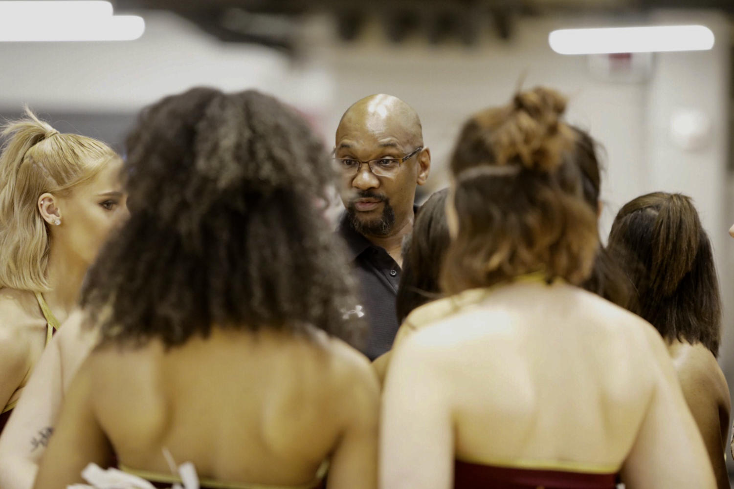 Cheer and dance head coach Rickey Hill addresses the dance team before a basketball game.