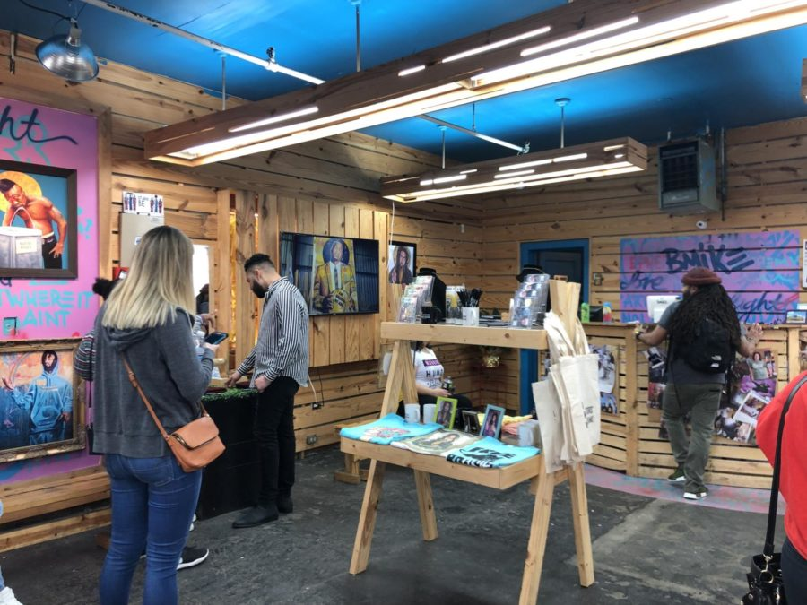 Loyola students browse the gift shop section of Studio BE. Studio BE sells many items ranging from t-shirts to customized spray cans. Photo credit: Shamaria Bell
