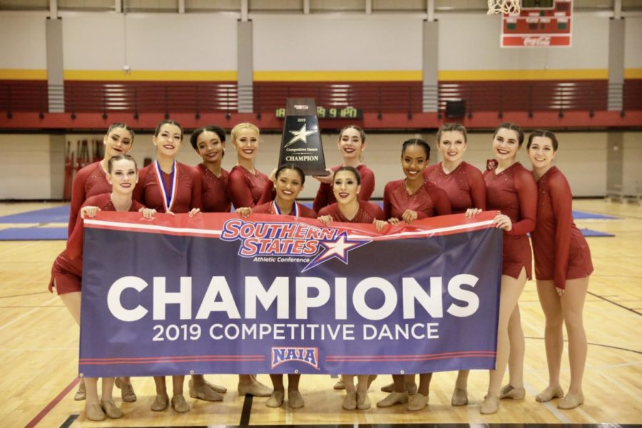 Loyola%27s+competitive+dance+team+poses+with+their+2019+championship+banner.+The+program+has+won+three-consecutive+conference+championships.+Photo+credit%3A+Ariel+Landry