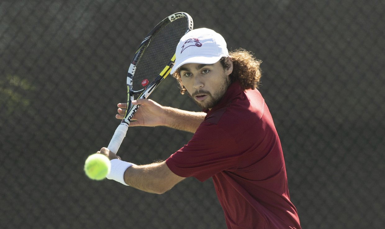 Biology senior Sebastian Gomez hits a tennis ball during warm ups. Both men and women's teams won two matches in a double-header. Photo credit: Loyola University Athletics