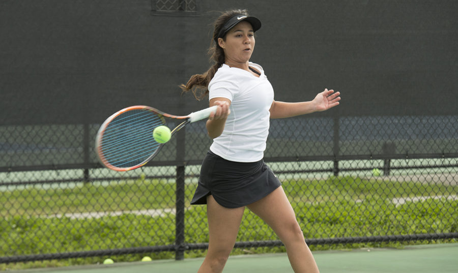 Biology senior Koral Martinez hits a tennis ball at City Park. Photo credit: Loyola New Orleans Athletics