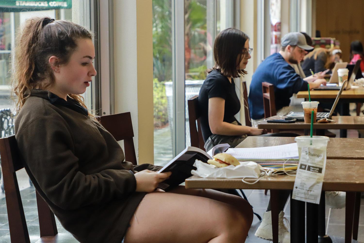 A Loyola student studies at Starbucks in the Danna Center with her coffee that she ordered using Tapingo. The express service allows students to order food and beverages ahead of time and pick them up at their convenience. Photo credit: Rob Noelke