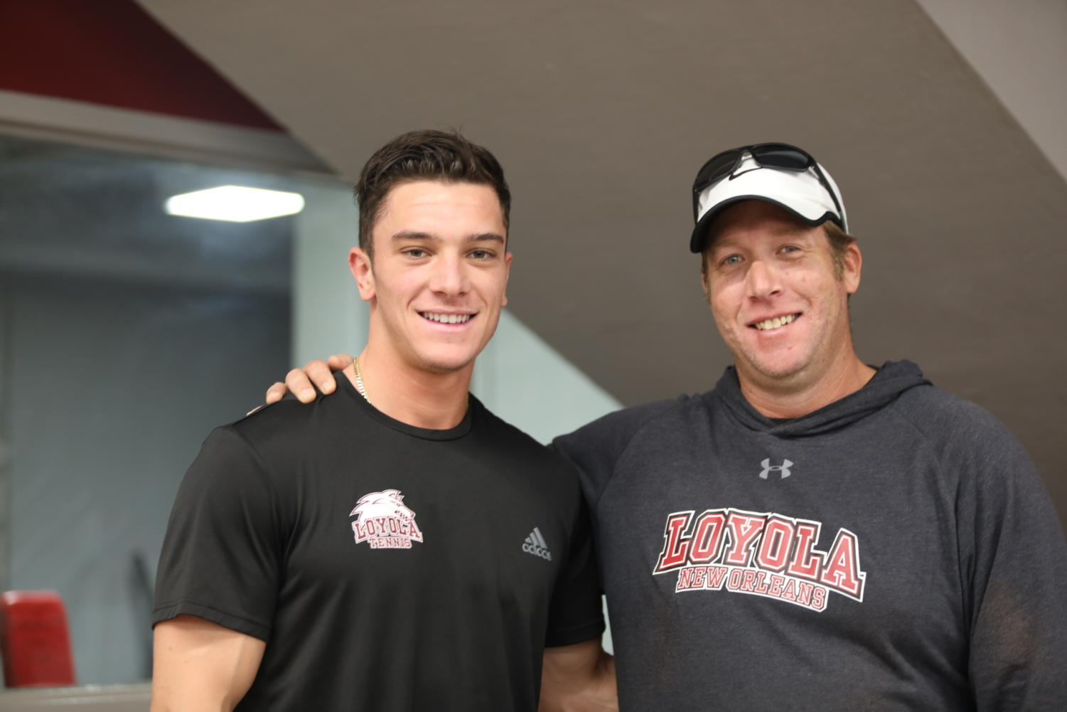 Marketing senior Sean Presti and tennis head coach Kyle Russell pose for a photo at The Den. The duo is cherishing their final year at Loyola together.