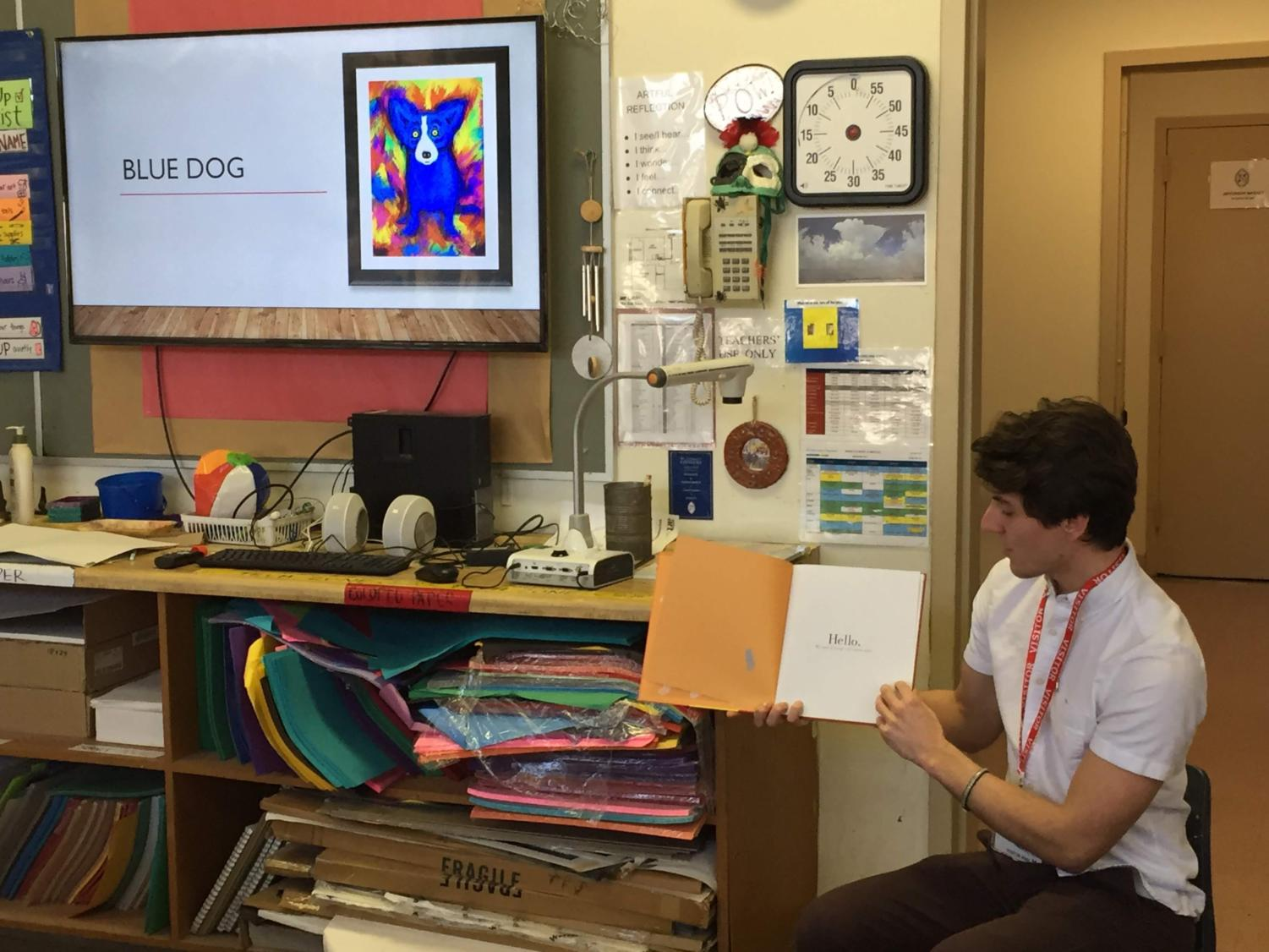 Robert Prasso, new member of Pi Kappa Phi fraternity, reads children's book to students at St. George's Episcopal Elementary School. Courtesy of Pamela Skehan.