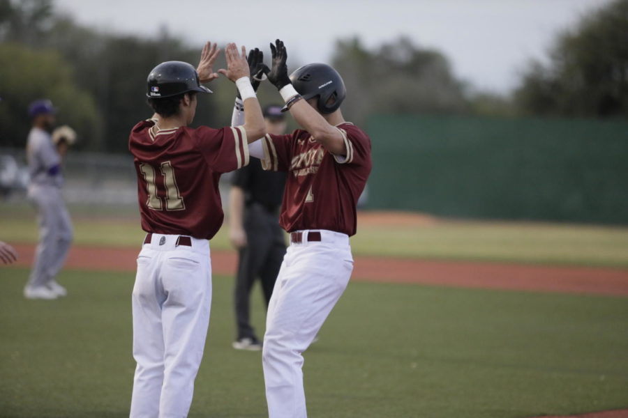 Biophysics+freshman+Derek+Oliveras+%2811%29+celebrates+with+biological+sciences+sophomore+Luke+Lacoste+%281%29+at+first+base.+Loyola+won+both+games+versus+Tougaloo+College.+Photo+credit%3A+Andres+Fuentes