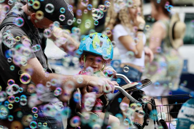 A father rides with his daughter in a bicycle through bubbles on Decatur Street. The French Quarter Fest prides itself on its family-friendly atmosphere.