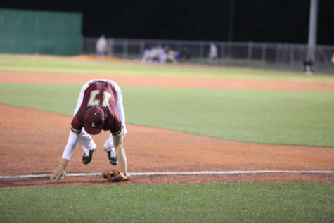 Business analytics freshman Patrick Chen See (17) falls after missing a foul ball. Loyola