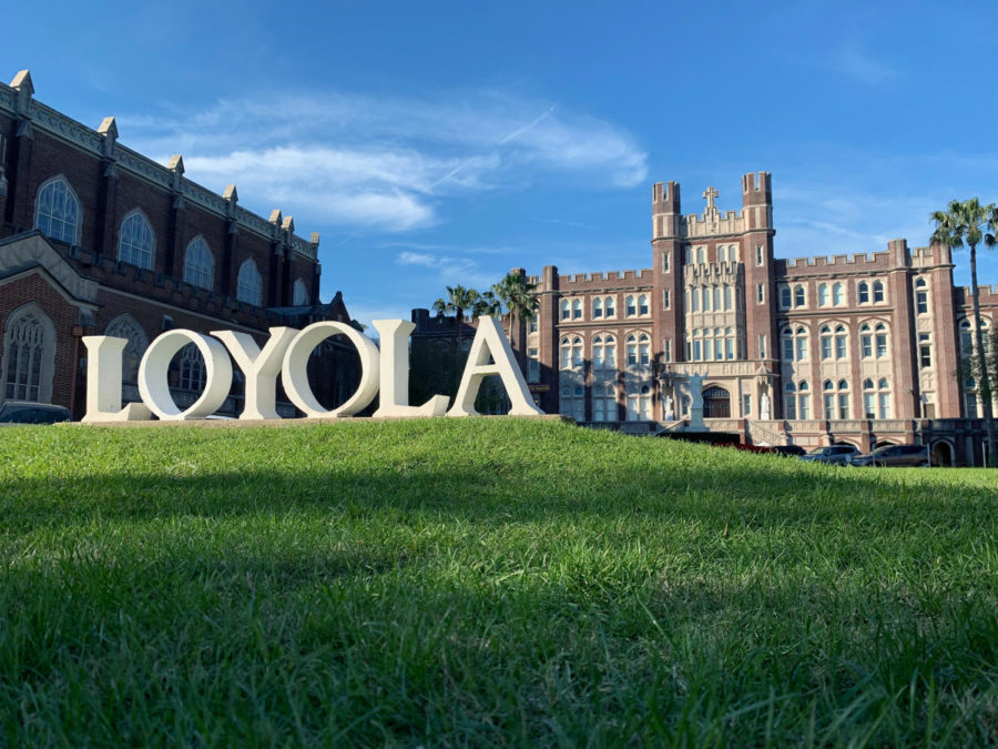 The Loyola sign sits in front of Marquette Hall on Loyola's campus on a sunny day