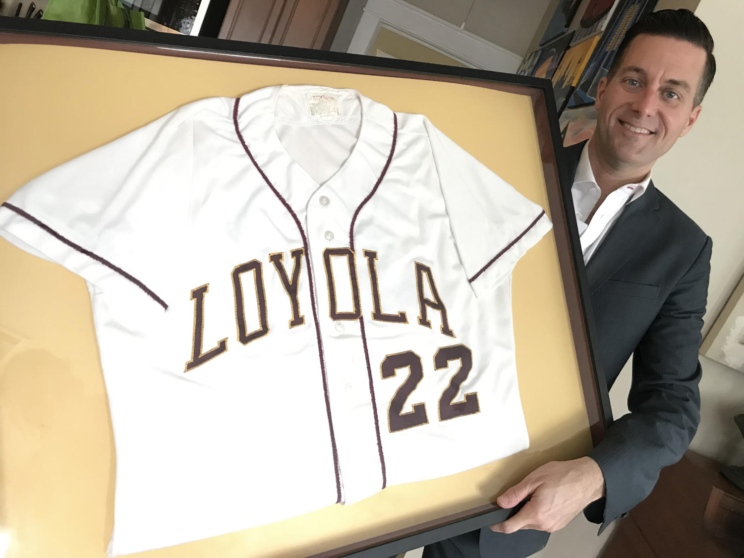 Fletcher Mackel poses with his framed Loyola jersey. He decided to frame his jersey after losing college memories during Hurricane Katrina. Courtesy of Fletcher Mackel.