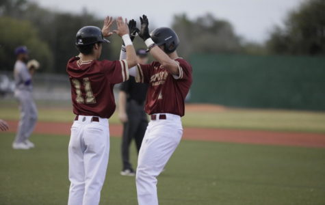 Biophysics freshman Derek Oliveras (11) celebrates with biological sciences sophomore Luke Lacoste (1) at first base. Loyola won both games versus Tougaloo College.