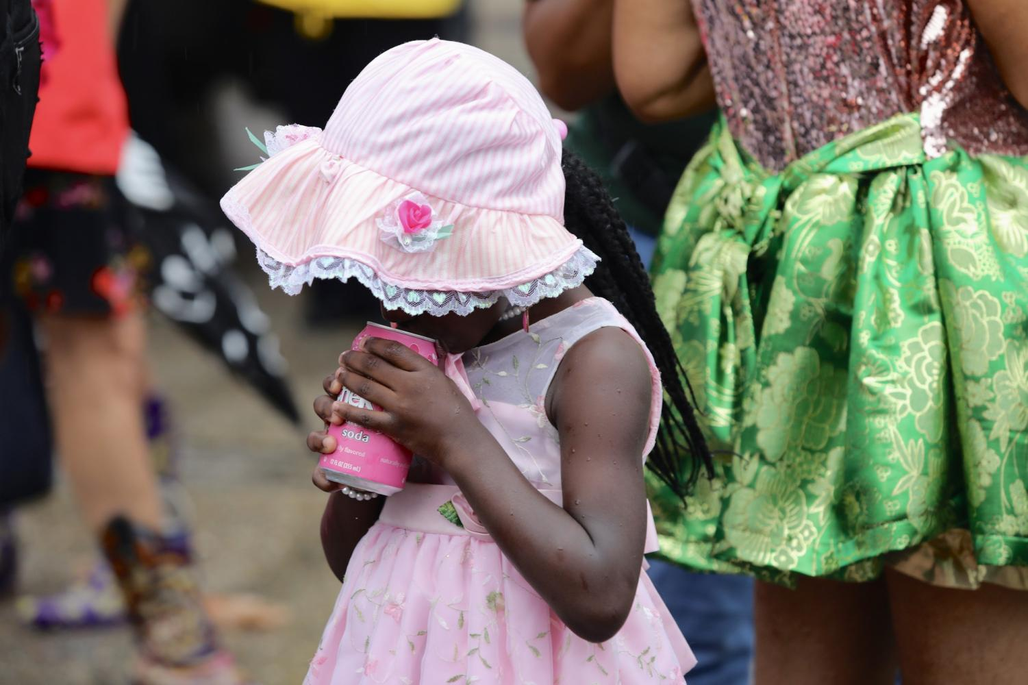 A baby doll cools down with a drink during Art Neville's second line procession on July 30, 2019. Photo credit: Andres Fuentes
