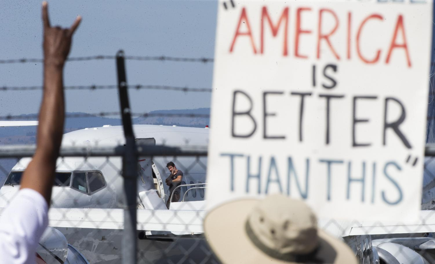 An ICE detainee waves at people chanting and holding signs along the fence while boarding a Swift Air flight on Tuesday, Aug. 20, 2019 at McCormick Air Center in Yakima, Wash. (Evan Abell / Yakima Herald-Republic via AP)/Yakima Herald-Republic via AP)