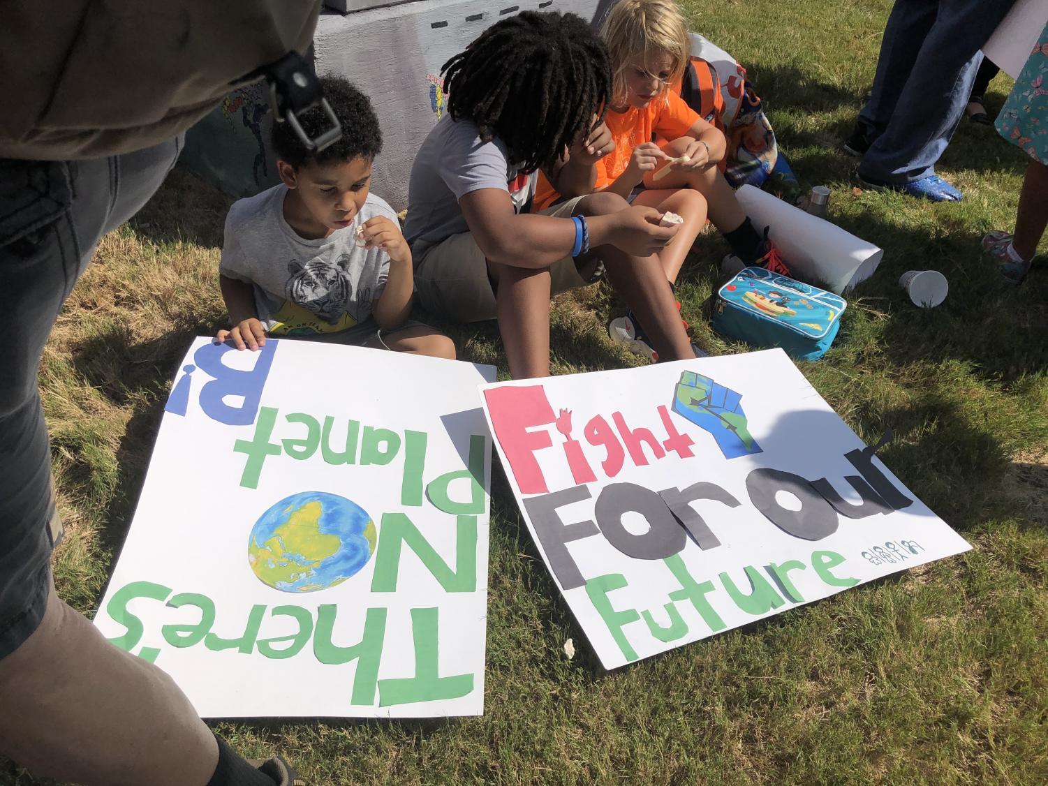 Children sit with signs at the New Orleans climate strike on Sept. 20. The strike was part of a week long protest that spread across six continents to raise awareness for climate change. Photo credit: Raegan Walberg
