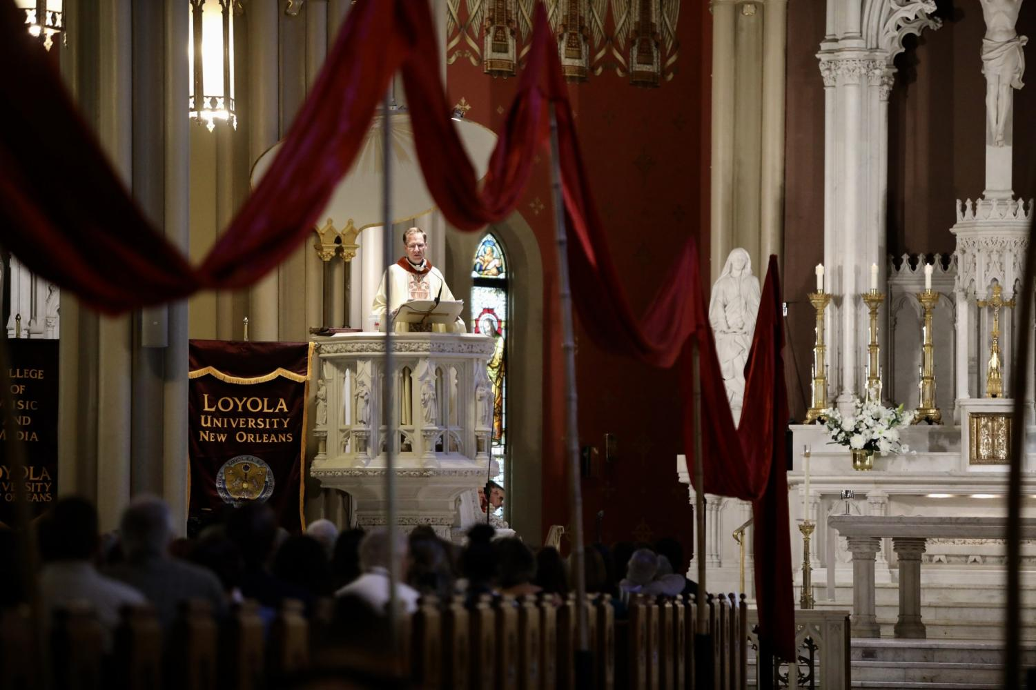 Red banners hang from poles all throughout the aisles of the Holy Name of Jesus church for the Mass of the Holy Spirit on September 5, 2019. The mass has an over 500 year old tie to Jesuit tradition. Photo credit: Andres Fuentes